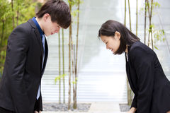 Young Asian business executives bowing to each other stock photo