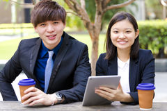 Young Asian business executives in discussion using table PC Royalty Free Stock Image