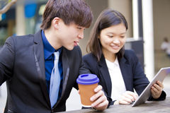 Young Asian business executives in discussion using table PC Royalty Free Stock Images