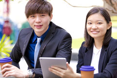 Young Asian business executives in discussion using table PC Stock Photography