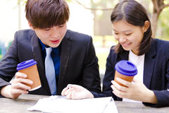 Young Asian business executives drinking coffee in discussion Royalty Free Stock Images