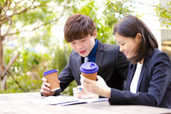 Young Asian business executives drinking coffee in discussion Stock Photos