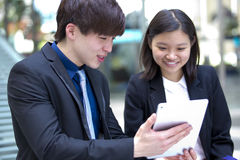 Young Asian business executives walking and discussing using tablet PC stock image