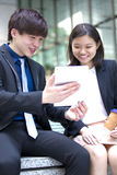 Young Asian business executives walking and discussing using tablet PC royalty free stock images
