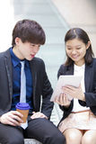 Young Asian business executives walking and discussing using tablet PC royalty free stock photography