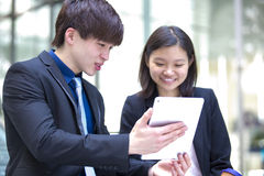 Young Asian business executives walking and discussing using tablet PC stock photos