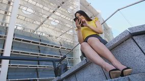Young asian business girl using mobile phone. Low angle view of young pretty asian business woman siting near business center steps in skirt and high heels and stock footage