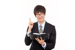 Young Asian business man with diary. Smilling young business man with diary Stock Photography
