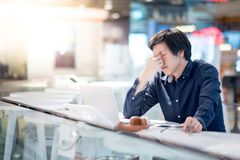 Young Asian business man feeling stressed while working with lap. Young Asian business man feeling stressed and frustrated while working with laptop computer royalty free stock photo