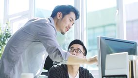 Young asian businessman getting help from coworker
