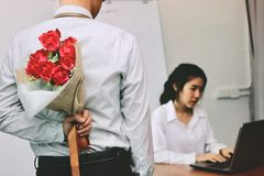 Young Asian business man holding a bouquet of red roses behind his back for girlfriend in valentines day. Love and romance in work Stock Image