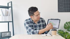 Young Asian business man leading remote video call conference meeting, look at camera, use digital tablet in home office