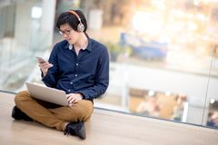 Young Asian business man listening to music while working with l Royalty Free Stock Photo