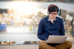 Young Asian business man listening to music while using laptop Royalty Free Stock Photos