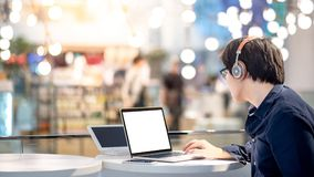 Young Asian business man listening to music while working with l. Young Asian business man listening to music by headphones while working with laptop computer in stock photography