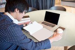 Young Asian man reading book in workspace of library. Young Asian business man reading book and magazine in workspace of library, freelance urban lifestyle Stock Images