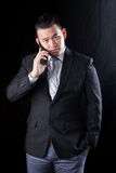 Young asian business man talking on mobile phone against black b Stock Photography