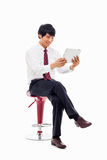 Young Asian business man using a pad PC sitting on the chair. Stock Images