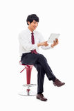 Young Asian business man using a pad PC sitting on the chair. Royalty Free Stock Image
