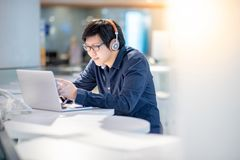 Young Asian business man using smartphone while working with lap stock photo
