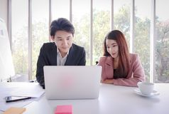 Young Asian business man work with laptop in the office. Young beautiful smile Asian business women with young Asian business men work with laptop in the office royalty free stock image