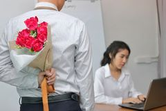 Young Asian business man holding a bouquet of red roses behind his back for girlfriend in valentines day. Love and romance in work. Young Asian business men Stock Image