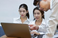 Young Asian business people working together on a laptop computer at office. Teamwork brainstroming concept. Selective focus and s. Hallow depth of field Royalty Free Stock Images