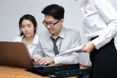 Young Asian business people working together on a laptop computer at office. Teamwork brainstroming concept. Selective focus and s. Hallow depth of field Stock Photo