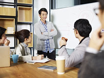 Young asian business person facilitating a discussion royalty free stock photo