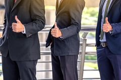 The young Asian business team stands with confidence and pride.They raise their thumbs at the same time. stock photo