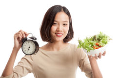 Young Asian business woman with clock and salad Royalty Free Stock Photography