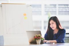 Young Asian business woman concentrated working to laptop on tab stock image