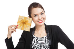 Young Asian business woman with a golden gift box. On white background Stock Photos