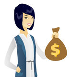 Young asian business woman holding a money bag. Happy asian business woman showing a money bag with dollar sign. Young successful business woman holding a money Royalty Free Stock Photos