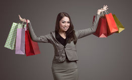 Young asian business woman holding shopping bag. Against gray background Stock Photography
