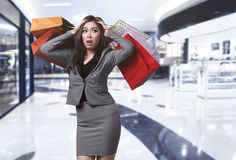 Young asian business woman with many bags looks shocked stock photos