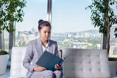 Young asian business woman with notebook in the office. In high floor in front of the window. The girl looks in the folder with the report Stock Images