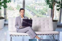 Young asian business woman with notebook in the office. In high floor in front of the window. Sitting on the couch Royalty Free Stock Photography