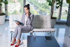 Young asian business woman with notebook in the office. In high floor in front of the window. Talking on the mobile phone Stock Images