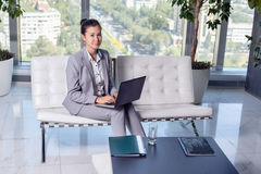 Young asian business woman with notebook in the office. In high floor in front of the window. Talking on the mobile phone Royalty Free Stock Photo