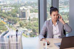 Young asian business woman with notebook in the office. In high floor in front of the window. Talking on the mobile phone Royalty Free Stock Photography