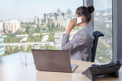 Young asian business woman with notebook in the office. In high floor in front of the window. Talking on the mobile phone Stock Photos