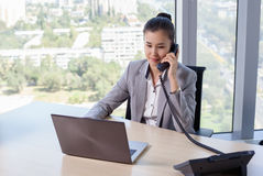 Young asian business woman with notebook in the office. In high floor in front of the window. Talking on the phone Stock Image