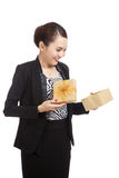 Young Asian business woman open a golden gift box. Isolated on white background Stock Image