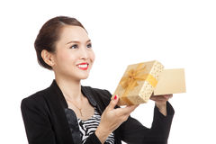 Young Asian business woman open a golden gift box. Isolated on white background Royalty Free Stock Images
