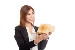 Young Asian business woman open a golden gift box. Isolated on white background Stock Photos