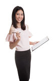 Young Asian business woman with pen and clipboard. Royalty Free Stock Photo
