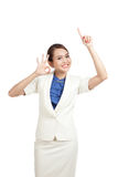 Young Asian business woman point up and show OK sign Stock Image