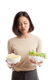 Young Asian business woman with potato chips and salad Royalty Free Stock Photos