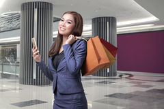 Young asian business woman with shopping bags holding mobile pho Stock Images